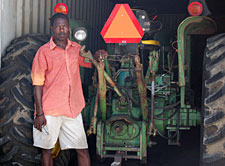 Haitian man proudly poses next to tractor.